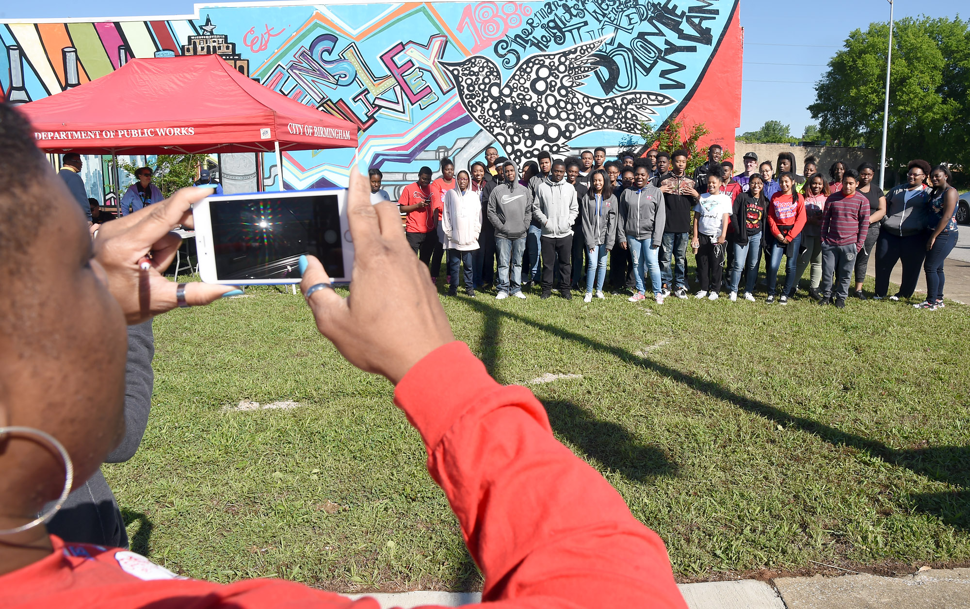 Teacher Maria Reese takes a picture of G.W. Carver High School students who participated in a clean up of the downtown Ensley area of Birmingham, Ala., Saturday, May 6, 2017. (Photo by Mark Almond)
