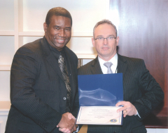 FBI Agent Ricky Maxwell presents Orrin C. Hudson with the FBI Director's Award for Community Leadership
