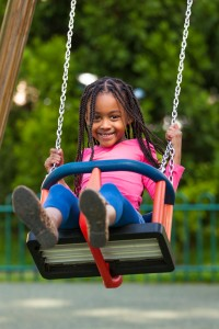 Outdoor  portrait of a cute young black girl playing with a swin