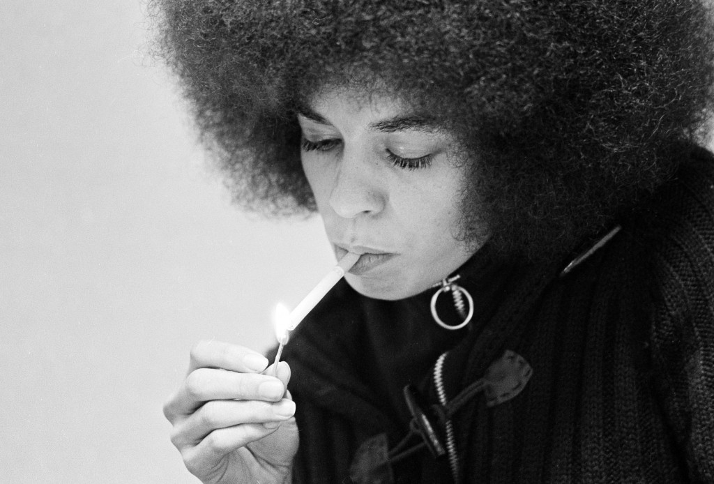 Angela Davis, black Communist jailed for more than a year on murder-conspiracy charges resulting from San Rafael courthouse slaying of a judge and three others, lights a cigarette as she talks during an exclusive interview with Associated Press reporters Edith Lederer and Jeannine Yoemans in tiny green interview room at Santa Clara County jail at Palo Alto, Dec. 27, 1971. (AP Photo/Sal Veder)