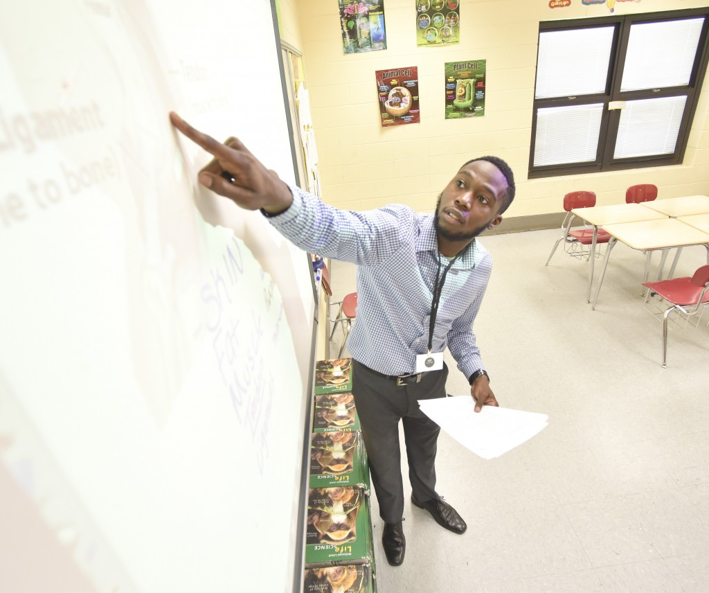 Mosley points to a diagram on a smart board in the classroom. Chris Mosely teaches a 7th grade pre-AP Biology class at Hudson K-8 in Collegeville. An initiative had been launched to recruit African American male teachers to Birmingham City Schools. (Frank Couch/The Birmingham Times)