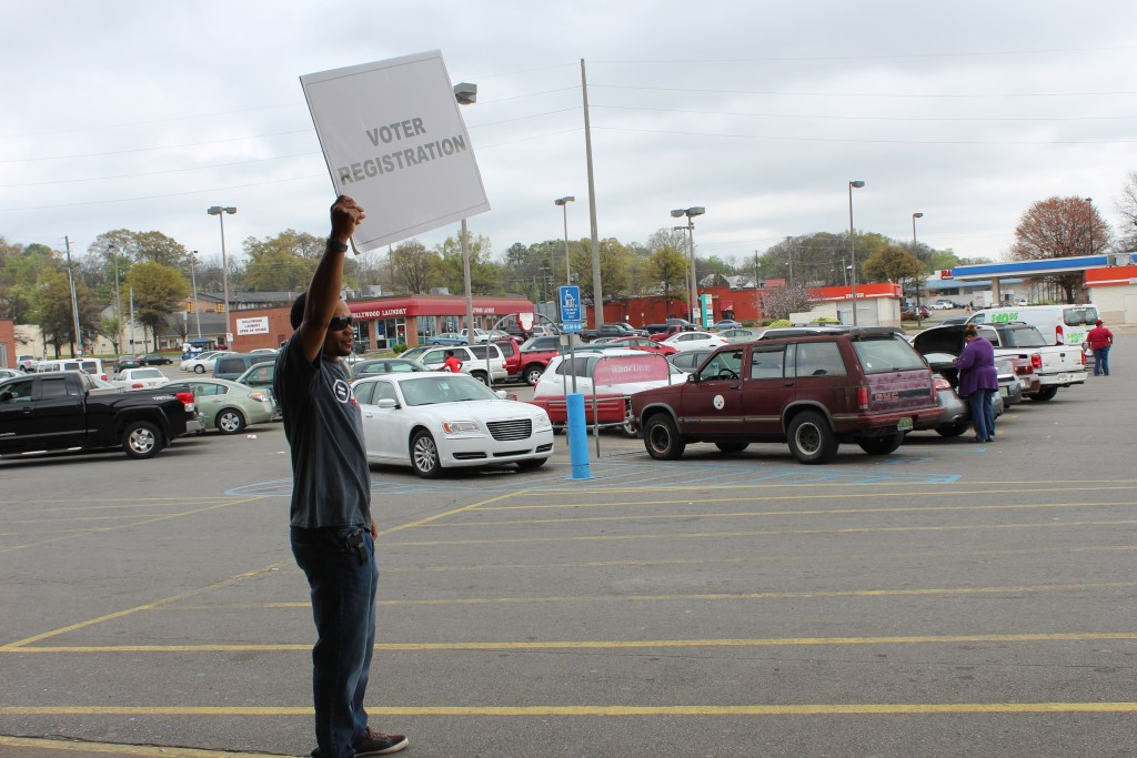 BULYP member Tamir Buford stands outside Winn Dixie in Five Points West to point the direction for voter registration