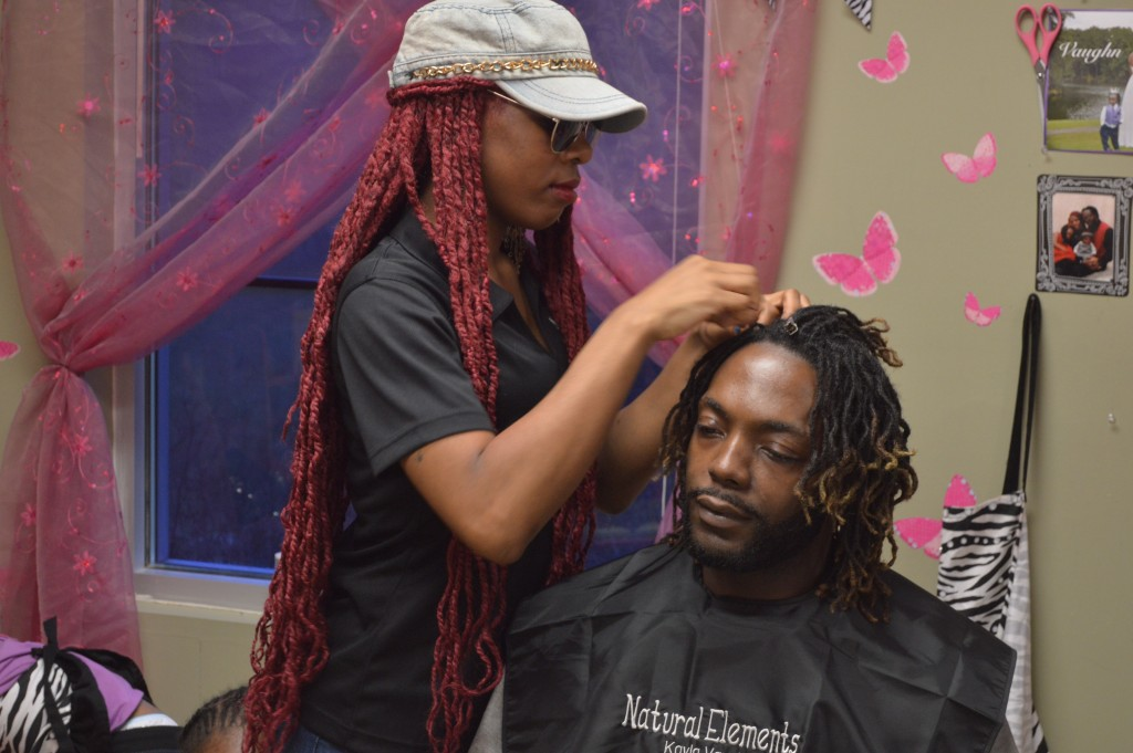 Natural hair stylist Kayla Vaughn re-locs her client Rico Vaughns hair. Kayla is a stylist at Natural Elements in Homewood.
