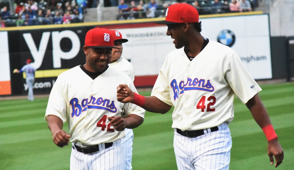 Eudy Pina (right) gives dap to teammate Marcus Lemon during evening to celebrate baseball great Jackie Robinson. (Solomon Crenshaw Jr. photo).