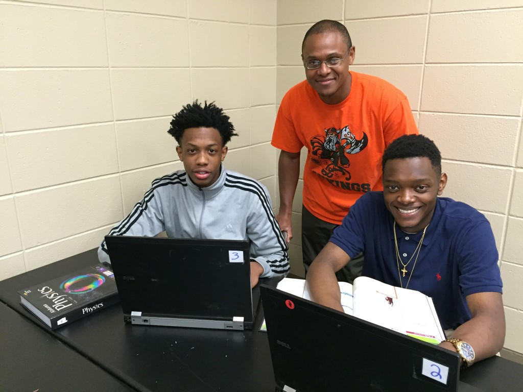 Huffman High science teacher with physics students Ronald Youngblood, left, and James Mullins on the newly donated laptops from Computers for Learning. Sanders, sponsor of the Robotics Team researched ways to secure funding to advance technology learning for students at his school. (Chanda Temple Photo, SPECIAL TO THE TIMES)