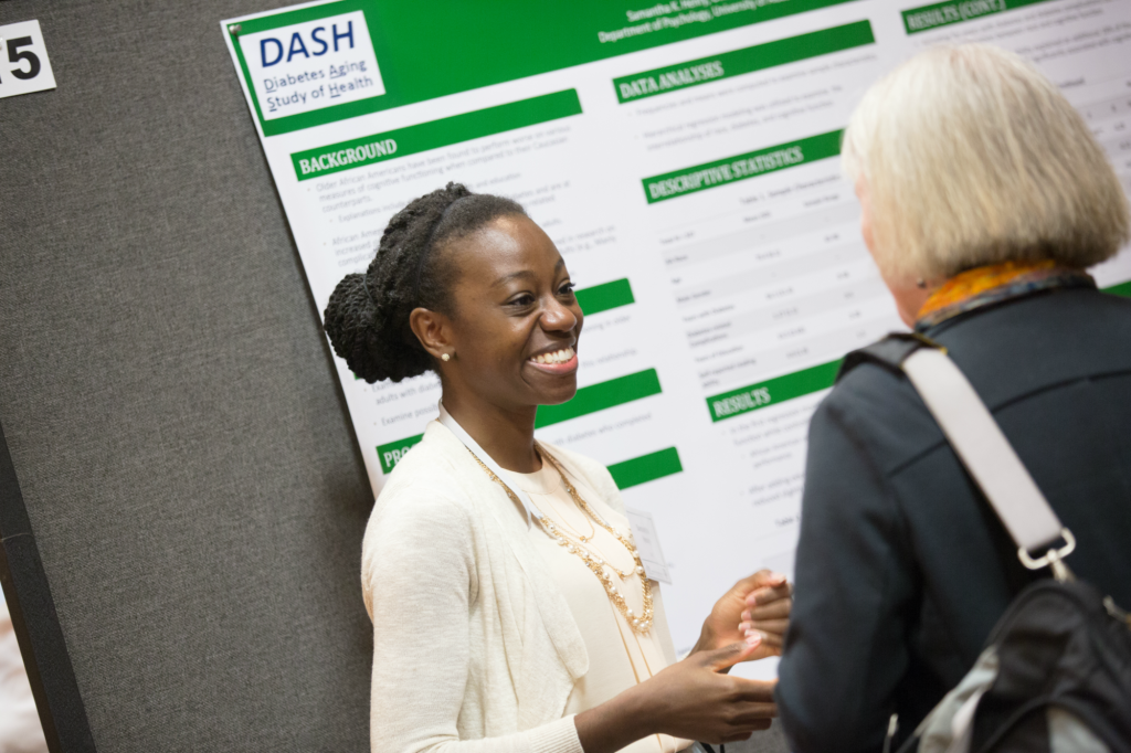 A student presents her diabetes research poster to a woman at an MHRC symposium. (PROVIDED PHOTO)