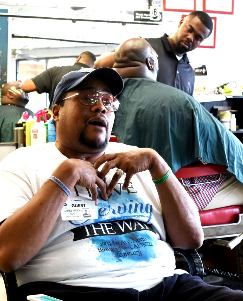 The Rev. James Mason talks as a patron gets a shave from shop owner Jimmy Shallow. (SOLOMON CRENSHAW JR. PHOTOS, FOR THE BIRMINGHAM TIMES)
