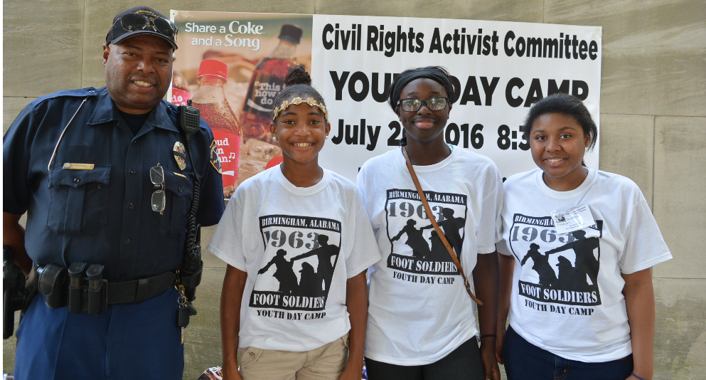 Officer Lawrence Billups with Chelsey  Cooley, of Hoover High School; Jada Repp, of Homewood High School and Brooklyn Kirksey, of Helena Middle School.