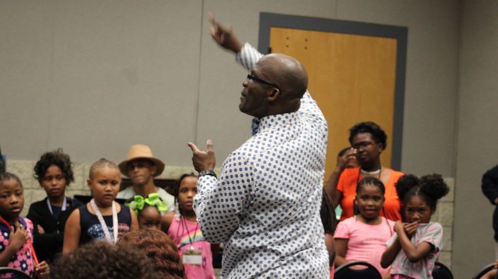 "Hugh Davis teaches the children of the GMWA conference the song ""God Made Me."" (Ariel Worthy, The Birmingham Times)"