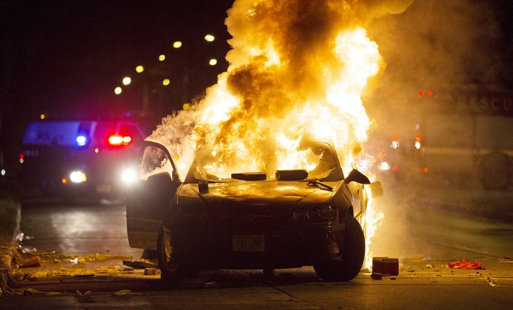 A car burns as a crowd of more than 100 people gathers following the fatal shooting of a man in Milwaukee, Saturday, Aug. 13, 2016. The Milwaukee Journal Sentinel reported that officers got in their cars to leave at one point, and some in the crowd started smashing a squad car's window, and another vehicle, pictured, was set on fire. The gathering occurred in the neighborhood where a Milwaukee officer shot and killed a man police say was armed hours earlier during a foot chase. (Calvin Mattheis, Milwaukee Journal-Sentinel via The Associated Press)