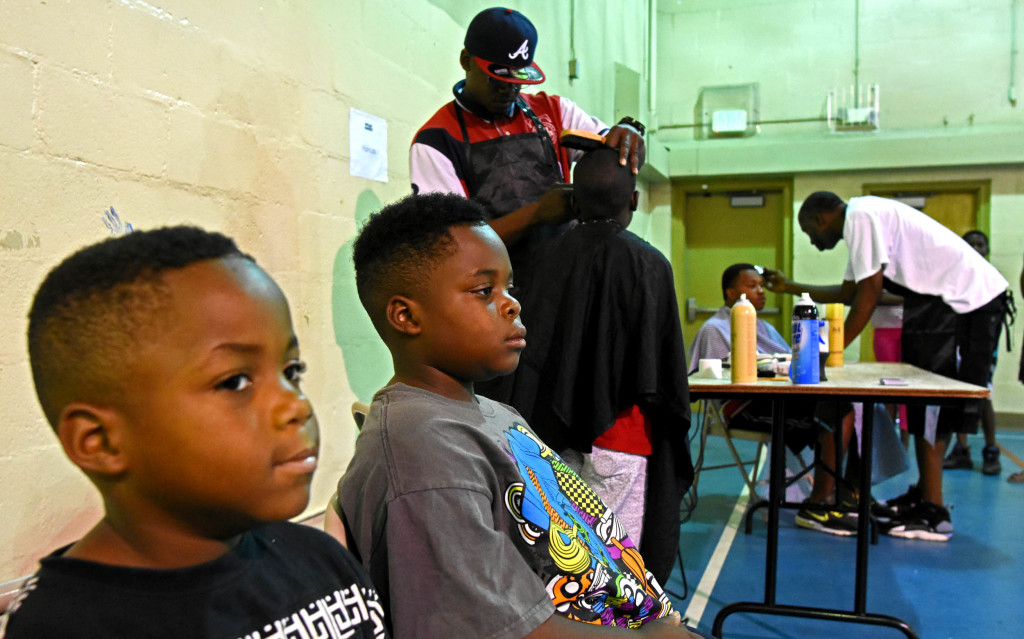 Brothers Jaylin and Aaron Caver wait for their cuts. (Solomon Crenshaw Jr photos, for The Birmingham Times)