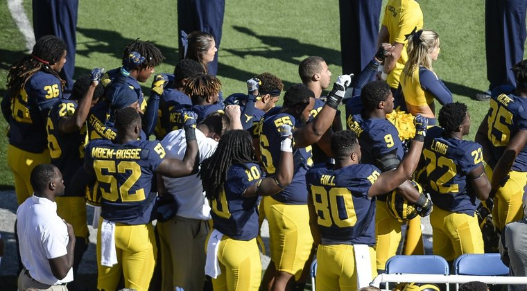Michigan football players raise fists in protest. (Courtesy The Shadow League)