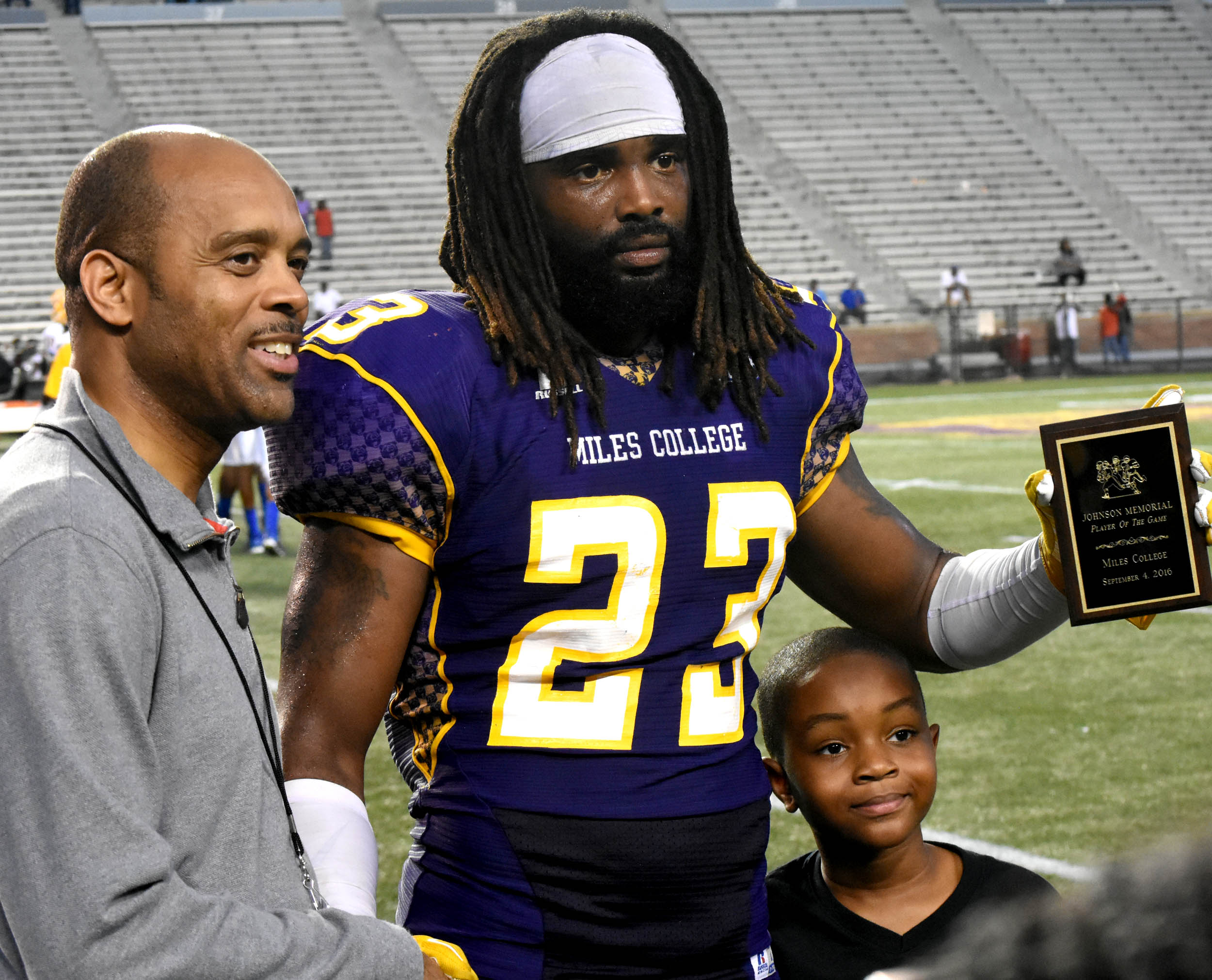 Miles College senior linebacker Emmanuel Ray earned most valuable player honors in the Labor Day Golden Classic on Sunday after the Golden Bears came from behind to beat Fort Valley State 34-21 at Legion Field. Ray receives the MVP award from Bessemer businessman Howard Johnson (left) owner of Johnson Funeral Home, who annually sponsors the MVP award. Johnson's 8-year-old son Michael is on the right. (Solomon Crenshaw Jr. photo).