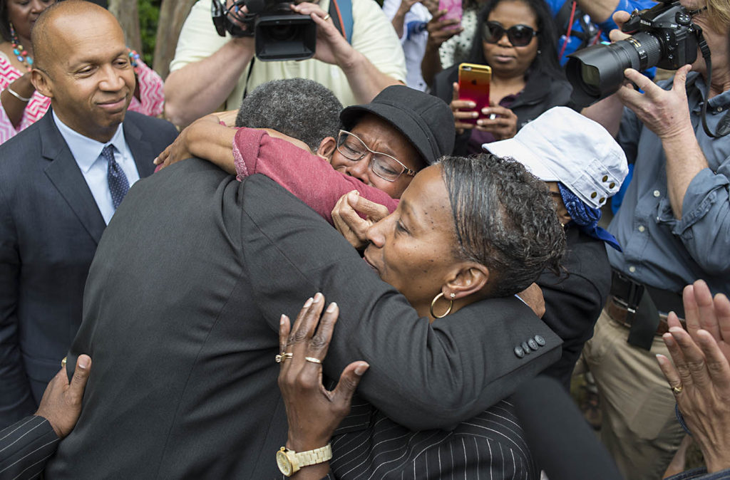 Members of the committee hug after the unveiling of a historical marker honoring the Domestic Slave Trade. (Bernard Troncale, special to The Times)