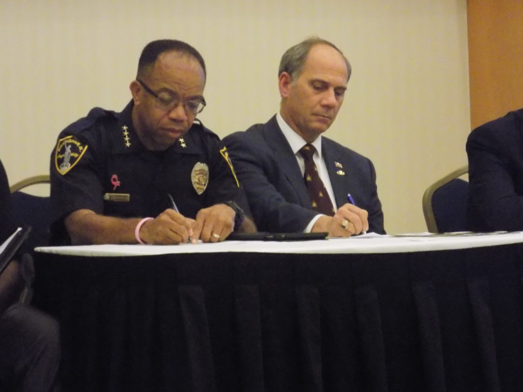 Birmingham Police Chief A.C. Roper (left) and Roger Stanton (right) take notes during the panel. (Monique Jones, The Birmingham Times)