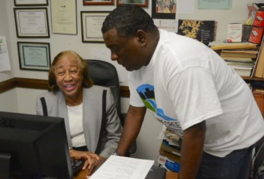 Village Creek Society founder Mable B. Anderson and Yohance Owens share a laugh at the VCS office. (Karim Shamsi-Basha, Alabama NewsCenter)