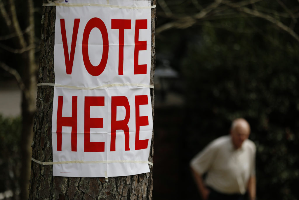 "A voter walks by a ""vote here"" sign after he cast his ballot in Alabama's primary at a polling site, Tuesday, March 1, 2016, in Birmingham, Ala. (AP Photo/Brynn Anderson)"