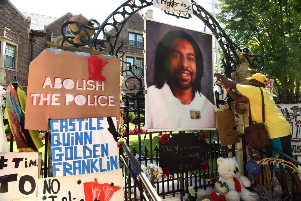 In this Sunday, July 24, 2016, file photo, King Demetrius Pendleton hangs a sign on the gate of the Governor's Residence in St. Paul, Minn., as protesters demonstrate against the July 6 shooting death of Philando Castile by a St. Anthony police officer making a traffic stop in Falcon Heights, Mich. The Minnesota Bureau of Criminal Apprehension has been investigating the shooting by St. Anthony police Officer Jeronimo Yanez of Castile. The agency said Wednesday, Sept. 28, that it turned over its findings to prosecutors. (Scott Takushi/St. Paul Pioneer Press via AP, File)