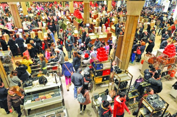 """People crowd the first floor of Macy's department store after they opened at midnight in New York to start the stores' """"Black Friday"""" shopping weekend. (Stan Honda, Creative Commons)"""
