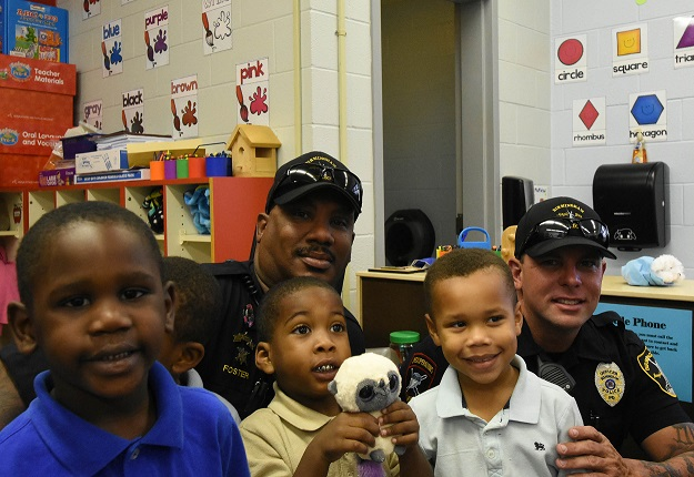 Officers Larry Foster (left) and Todd Sutherland visit with Hemphill students Jacoby Woodgett-Davis, Deon Cunningham-Buchannon and Hillman Tubbs. (Solomon Crenshaw Jr., special to The Times)