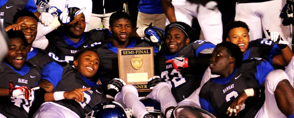 Ramsay High football players pose with the trophy they earned by winning their Class 6A semifinal 25-14 over Austin on Friday, Nov. 25, 2016, at Birmingham's Lawson Field Stadium. The victory sends the Rams to the state championship game against Opelika at Auburn's Jordan-Hare Stadium. (Ariel Worthy, The Birmingham Times)