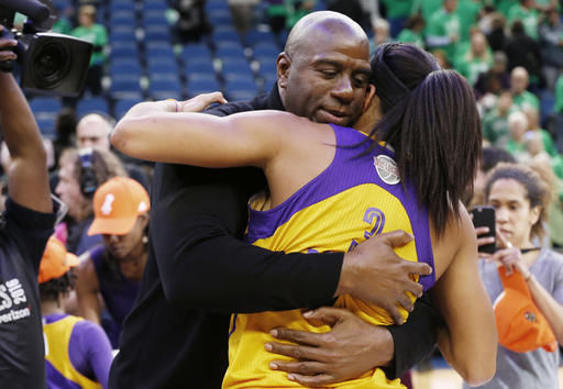 In this Oct. 20, 2016, file photo, Los Angeles Sparks owner Magic Johnson, left, hugs Candace Parker after the Sparks won the WNBA basketball championship title with a win over the Minnesota Lynx, in Minneapolis. The WNBA has been the sports industry gold standard when it comes to gender and racial hiring practices. And it appears that won't change this year with the WNBA scoring an A+ in both gender and racial hiring practices in the latest of Richard Lapchick's Racial & Gender Report Card. (AP Photo/Jim Mone, File)