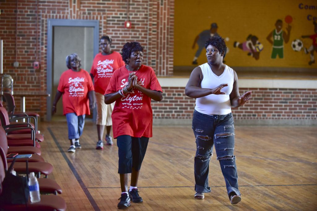 From left, Gloria Sanders, Melinda Ruffin, Delia Mitchell and Tracey Moore take a lap around the gym during Walk Club. (Frank Couch, The Birmingham Times)