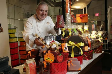 In this Thursday, Nov. 10, 2016, photo, Jacques Torres, who sells his well-known and high-end chocolate and other food at eight locations in New York and online, assembles a gift basket at his flagship store in New York. Torres, whose chocolates retail for nearly $40 a pound, has a lot of competition and rising expenses like rent and wages. He plans a special promotion with a sandwich, beverage and ice cream for $10 at his cafe in Grand Central Terminal. (AP Photo/Richard Drew)