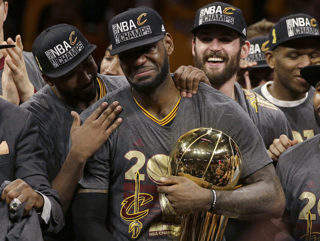 In this June 19, 2016, file photo, Cleveland Cavaliers forward LeBron James, center, celebrates with teammates, including Kevin Love, third from left, after Game 7 of basketball's NBA Finals against the Golden State Warriors in Oakland, Calif. James delivered on his personal pledge to bring home a title in June. (Marcio Jose Sanchez, Associated Press, File)