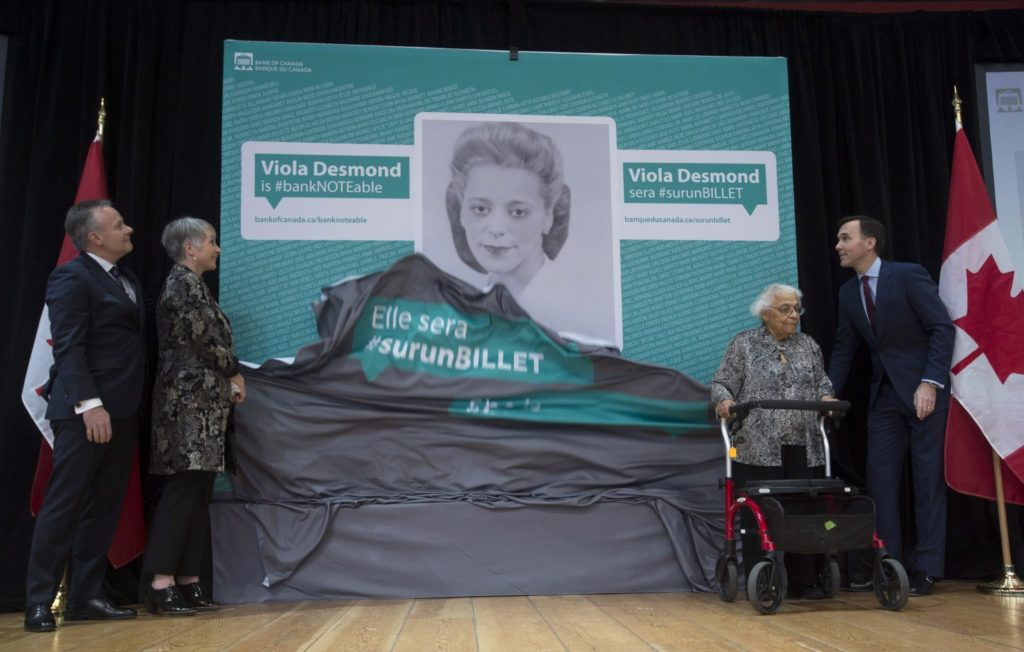 Bank of Canada Governor Stephen Poloz, left, Minister of Status of Women Patricia Hajdu, Minister of Finance Bill Morneau, right, and Wanda Robson unveil an image of Viola Desmond who will be featured on the new Canadian ten dollar bill during a ceremony in Gatineau, Quebec, Canada Thursday. Robson is Viola Desmond's sister. (Adrian Wyld, Associated Press)