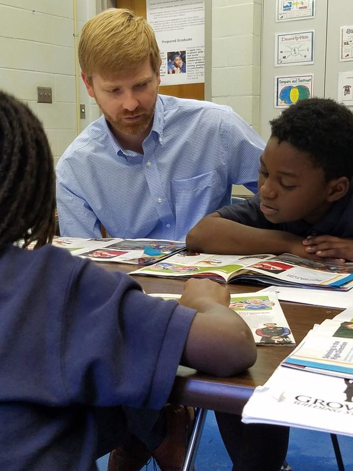 Tal Simpson, attorney at Balch & Bingham LLP, reads a magazine with one of the Growing Kings students. (Provided photo)