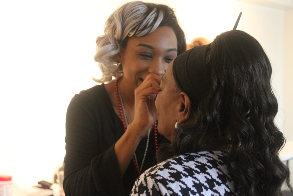 Independent make up artist Somica Spratley talks with a client as she does her make up for Hope Portrait Birmingham. (Provided photo)