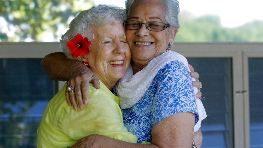 In this Friday, Nov. 18, 2016 photo, Joan Rodby, 85, left, and Emma Veary, 86, hug during a reunion in Makawao, Hawaii. After the Pearl Harbor attack, their schools required them to carry gas masks with them at all times. (Rick Bowmer, Associated Press)