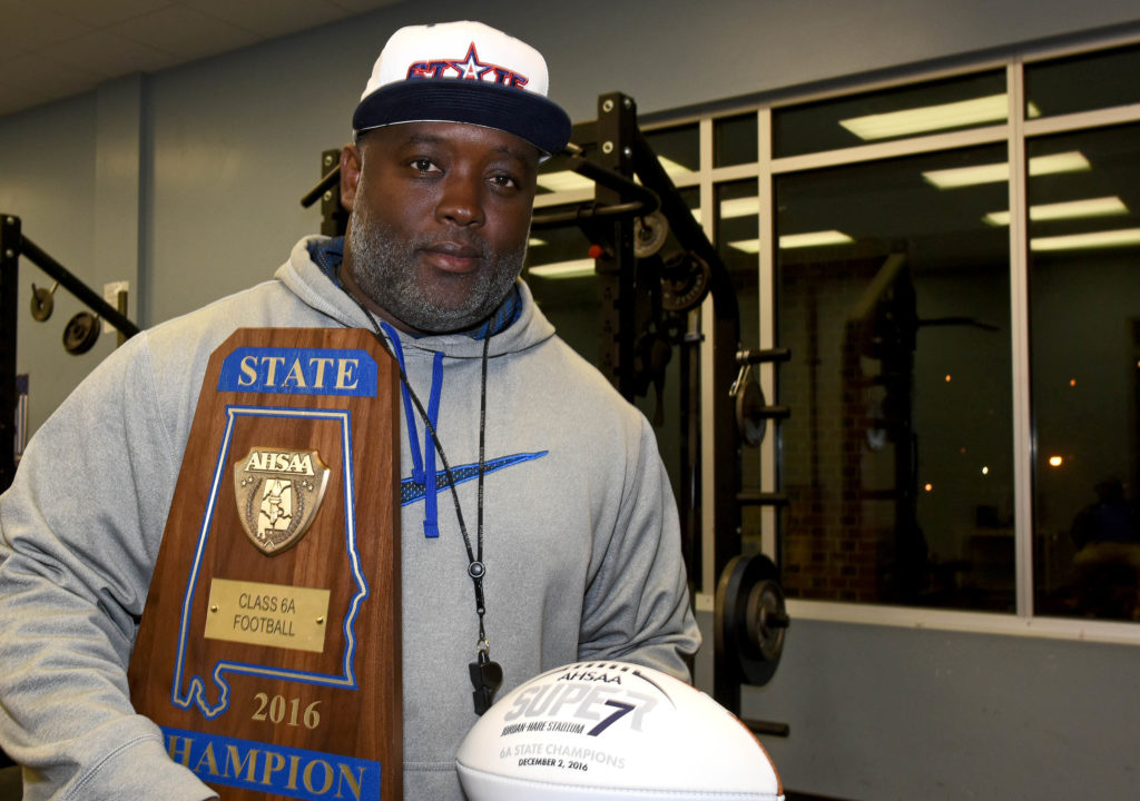 Coach Rueben Nelson Jr. cradles the championship trophy and football he received after his Ramsay Rams defeated Opelika 21-16 in Jordan-Hare Stadium  to win the Class 6A Alabama High School Athletic Association state football championship on Friday, Dec. 2, 2016. (Solomon Crenshaw Jr., special to The Times)
