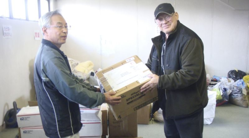 Joseph Roginski, right, holds a package in a storeroom of the Misawa City Hall in Japan. The former military language and intelligence specialist said he pays $350 annually to be part of Japan's national health insurance. His policy covers 70 percent of his costs. The rest is covered by a secondary insurance program for retired military personnel. (Joseph Roginski, Associated Press)