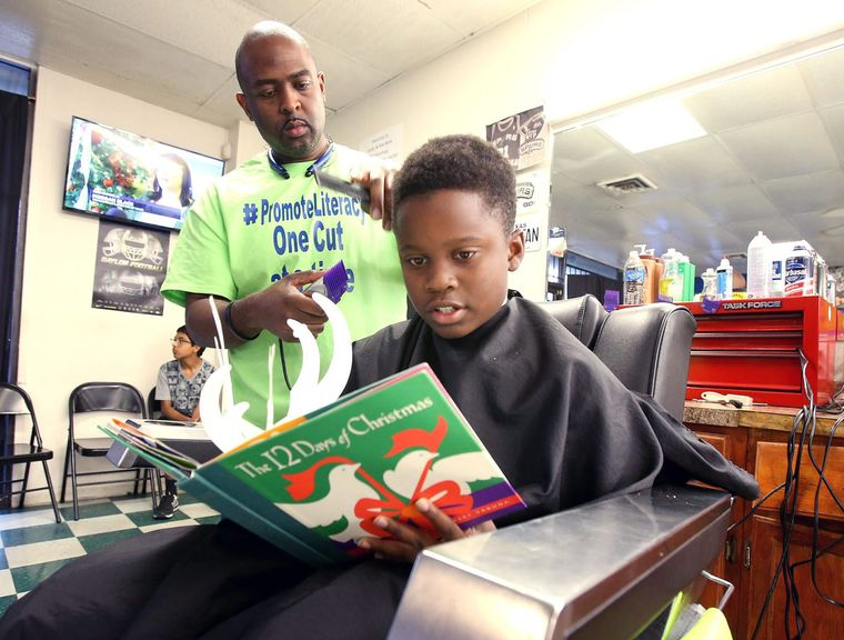 Fourth-grader Noah Jimerson, 10, reads as barber Ivan LeBlanc at Look At Me Now Barbershop cuts his hair. LeBlanc is offering kids $2 if they read to him during their haircut. (Provided photo)