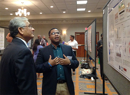 Upender Manne, left, UAB's lead principal investigator for the UAB Cancer Center/Morehouse School of Medicine/Tuskegee University partnership, discusses cancer disparities with a researcher at a poster presentation. (Provided photo)