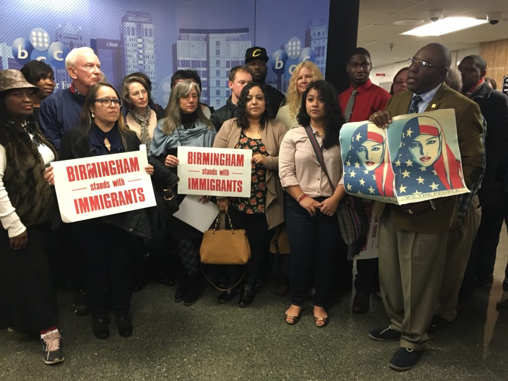 Protesters including Sarai Portillo, executive director of the Alabama Coalition for Immigrant Justice (left), Carlos Chaverst of the Birmingham chapter of the National Action Network (right) and Frank Matthews, founder of the Outcast Voters League (far right) hold an impromptu press conference after the City Council passes the resolution to declare Birmingham a sanctuary city. (Monique Jones, The Birmingham Times)