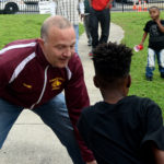 Christopher Nanni, President and CEO of the Community Foundation of Greater Birmingham, plays a little one-on-one with a youngster attending the tour event at Southtown public housing community. (Solomon Crenshaw Jr., for The Birmingham Times)
