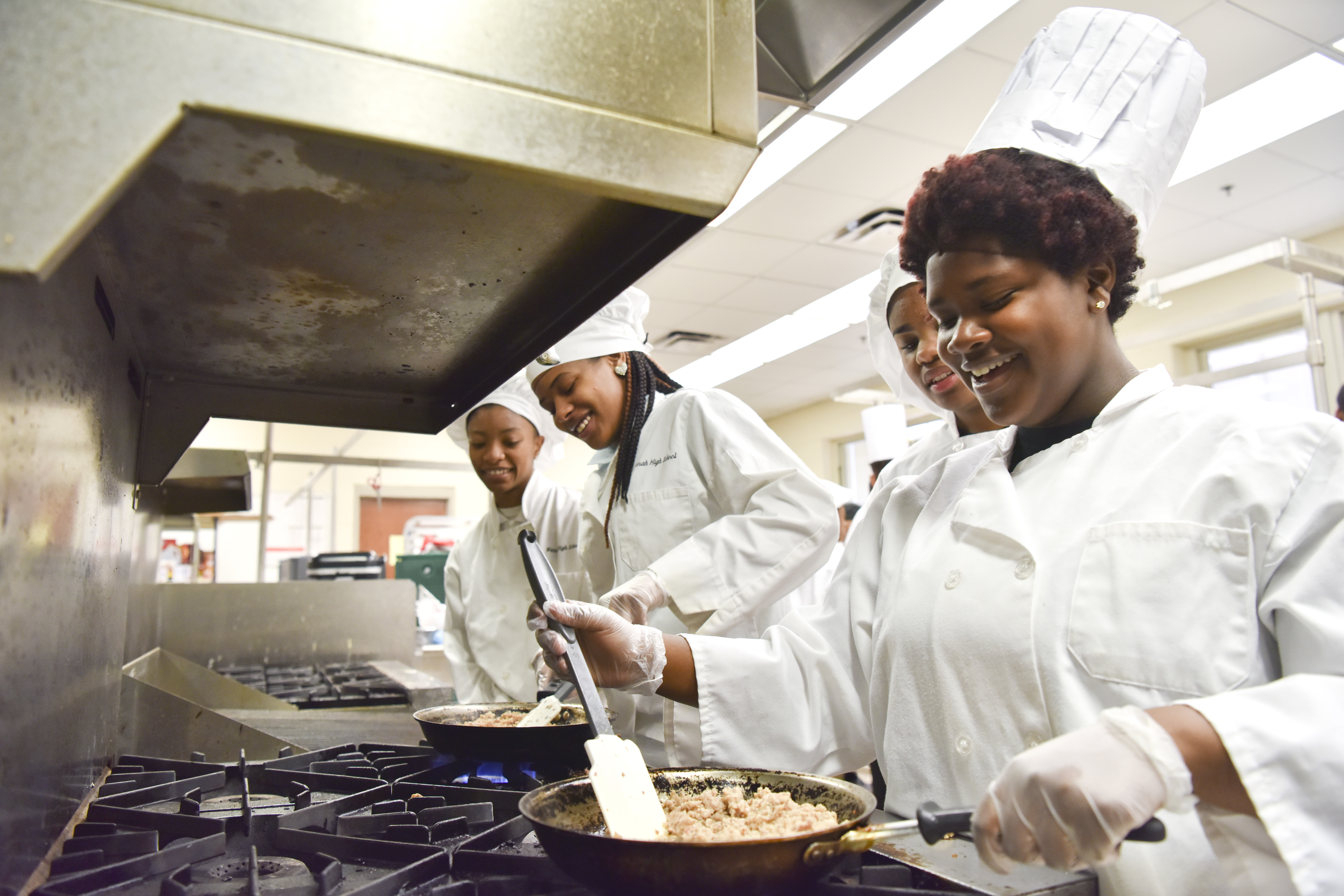 Kumari Burns, Destiny Myricks and Aundreia Moore brown sausage on the stove in the kitchen. The Wenonah High School Culinary Arts program teaches students commercial kitchen skills (Frank Couch,The Birmingham Times)