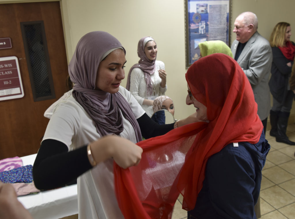 Tala Samour helps Karen Arnold with a Hajib, a traditional head covering as part of the information session. (Frank Couch,The Birmingham Times )