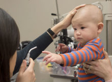 Becky Luu, O.D., checks six month old infant's eye coordination. The infant shows that he can reach for an object, an important six month developmental milestone, and that he has very useful 3-D vision.  (UAB)