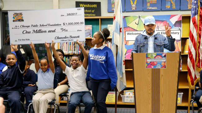 Chance The Rapper, right, announces a gift of $1 million to the Chicago Public School Foundation during a news conference at the Westcott Elementary School, Monday in Chicago. The Grammy-winning artist is calling on Illinois Gov. Bruce Rauner to use executive powers to better fund Chicago Public Schools. (Charles Rex Arbogast, Associated Press)