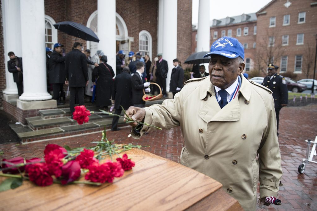 Tuskegee Airman Eugene J. Richardson Jr., places a flower on the casket containing the remains of his comrade John L. Harrison, Jr., after Harrison's a funeral mass at the Chapel of the Four Chaplains in Philadelphia, Friday, March 31, 2017.  Harrison Jr. became one of America's first black military airmen, one of nearly 1,000 pilots who trained as a segregated unit with the Army Air Forces at an airfield near Tuskegee, Ala. (Matt Rourke, Associated Press)