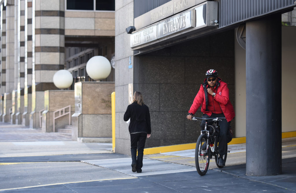 CAP officer Eugene McCoy rides a bike on patrol after helping a motorist unlock a car in a parking deck. (Frank Couch, The Birmingham Times)