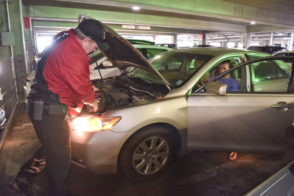 CAP daytime supervisor Jimmy Swindle uses a portable battery to jump start the car of Stacy Justice in a parking deck near Children's of Alabama. (Frank Couch, The Birmingham Times)
