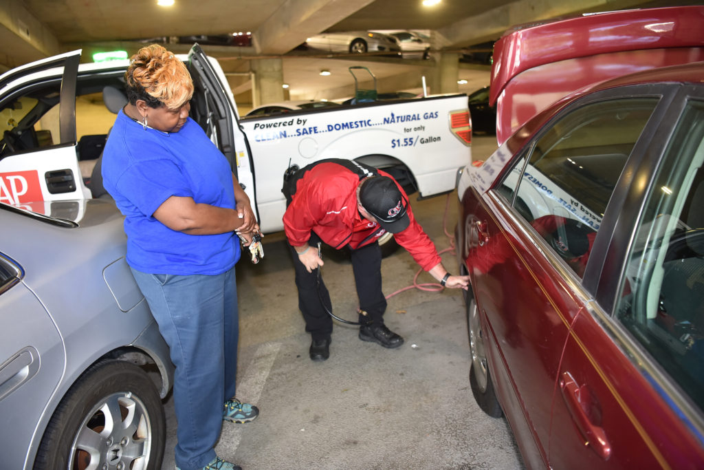 CAP daytime supervisor Jimmy Swindle checks the tire of Jackie Thomas who called after discovering a flat tire. (Frank Couch, The Birmingham Times)