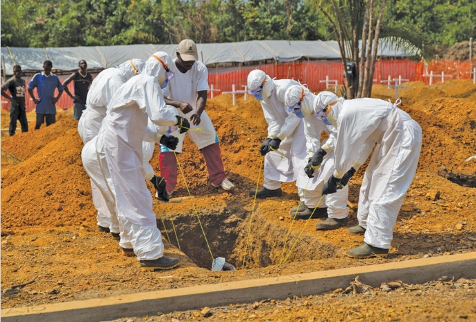 A burial team lowers the body of an Ebola victim into a grave in a new cemetery in Liberia. (Unmeer photo)