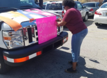 Felicia Huntley, Interim Resident Services Administrator, decorates a housing authority bus Tuesday afternoon as teams prepare to visit multiple public housing communities to promote the Women's Empowerment Conference. (Darryl Washington, HABD photo)