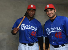 Designated hitter Keon Barnum, left, and first baseman Nick Basto share a moment in the dugout before their Jackie Robinson Day game against the Montgomery Biscuits on Saturday, April 15, 2017. Barnum opened the scoring with a home run as the Barons won, 5-2, with all members of the home team wearing No. 42. (Solomon Crenshaw Jr., for The Birmingham Times)
